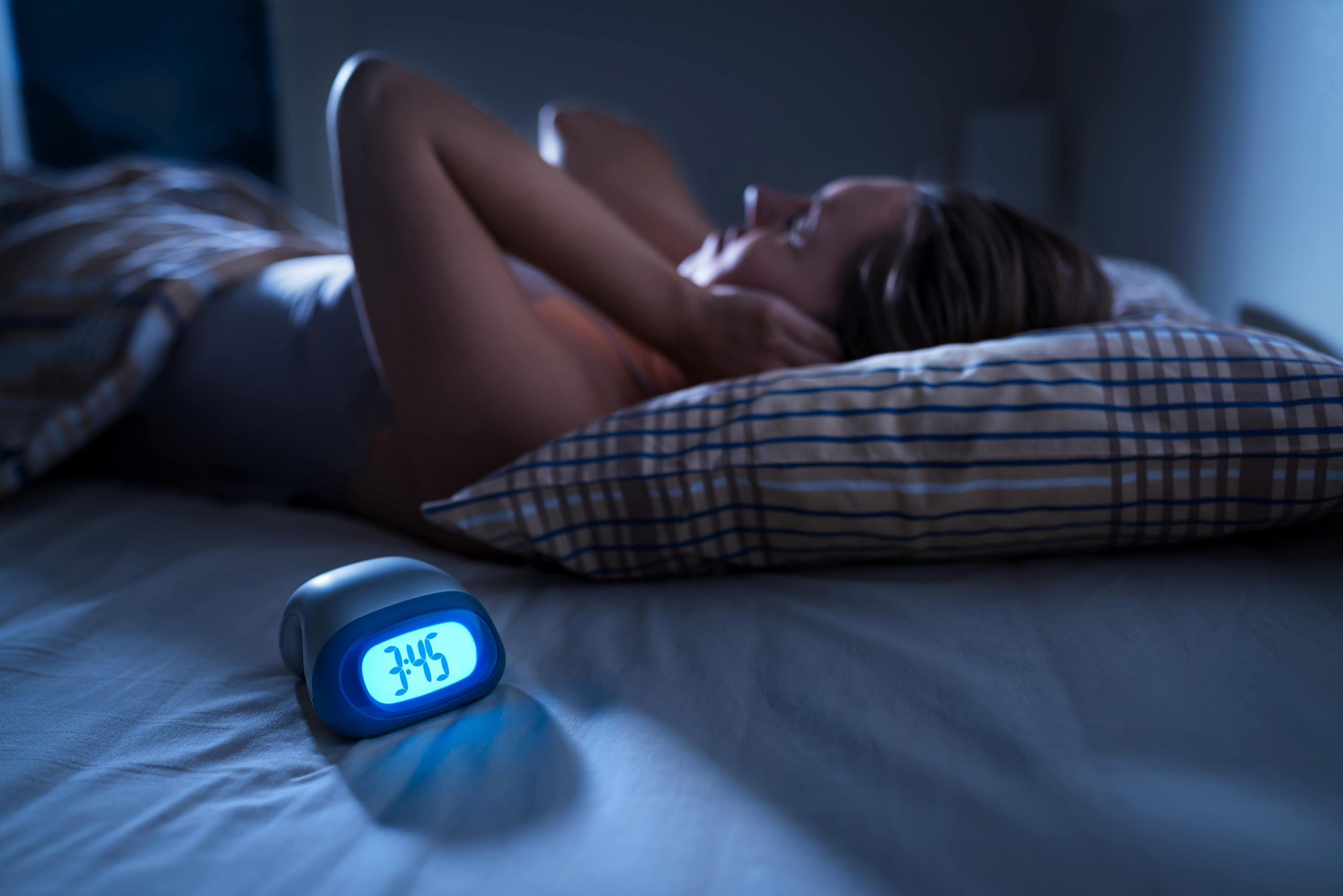 woman lying in bed unable to sleep because of tinnitus