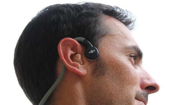 Man wearing hearings aids with bone conduction headphones